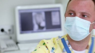 Dentist in medical mask moves light in dental surgery — Stock Video