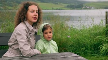 Mother with her little daughter sit at background of lake — Vídeo de Stock