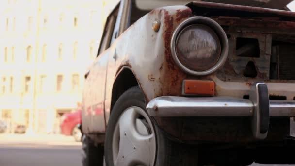 Viejo soporte coche oxidado en la calle con tráfico en día soleado — Vídeo de stock