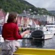 Woman sits on quay in dock with boats in coastal Bergen town — Stock Video
