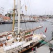 People walk on pier near sailing ships which profits on regatta — Видео