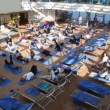 People lie in hall on deck of ship and together do exercises — Stock Video