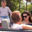 Students in sunglasses and two kids sit in cabriolet — Stock Video #32350363