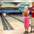 Kids stand in bowling club, then girl walks away, boy make throw — Stock Video #32350407