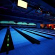 Ball rolls and beats skittles on bowling lane with illumination — Stockvideo