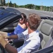 Stock Video: Young pair ride backward in cabriolet on street at sunny day
