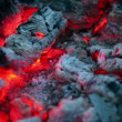 Stock Video: Flicker of smoldering embers lay in ashes, closeup view