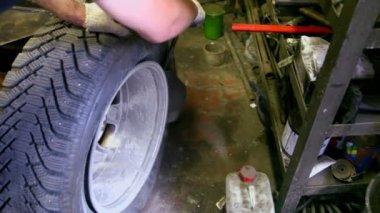 Człowiek odłożyć opon z koła samochodu przez specjalne narzędzie, widok zbliżenie — Wideo stockowe