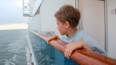 Boy looks at water, leaning on handrail of board of ship — 图库视频影像