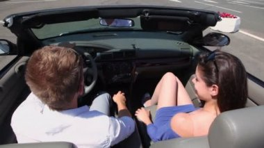 Young couple ride in cabriolet by road, behind view from above — Stock Video