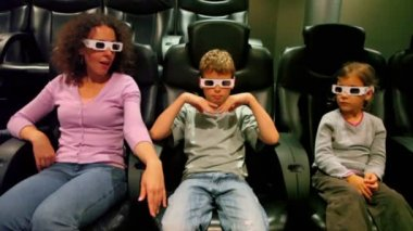 Two kids with their mother in 3d stereo glasses sit at cinema — Stock Video