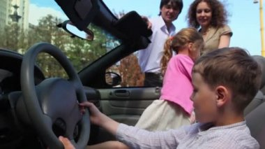 Two kids boy with girl play in cabriolet and parents stand near — Stock Video