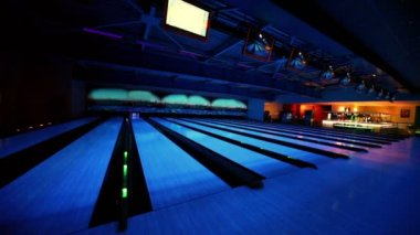 Ball rolls and beats skittles on bowling lane with illumination in dark club