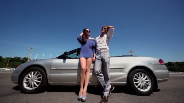 Young couple in sunglasses stand near cabriolet at summer day — Stock Video
