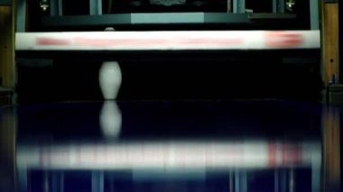 Bowling ball rolls and beats tenpins lit in dark, closeup view — Stock Video