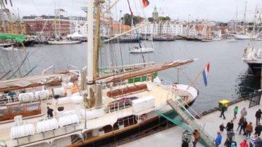 People walk on pier near sailing ships on regatta — Stock Video