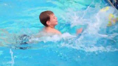 Liten pojke simmar i poolen och spela med uppblåst boll — Stockvideo