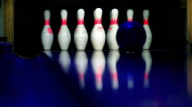 Bowling ball rolls and beats skittles lit in dark, closeup view — Stock Video
