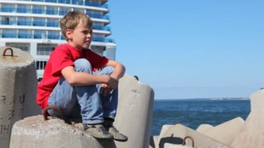 Boy sits on concrete breakwater against white liner — Stock Video