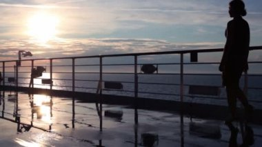 Silhouette of woman walks by deck and watch sunset during cruise — Stock Video