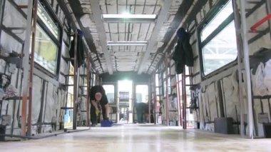 Worker screws up screws of screwdriver in floor of wagon — Stock Video