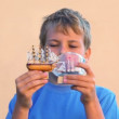 Stock Video: Boy looks at models of tall ships in bottles and moves them