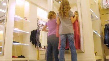 Girls in front of mirror try on dresses in shop, time lapse — Stock Video