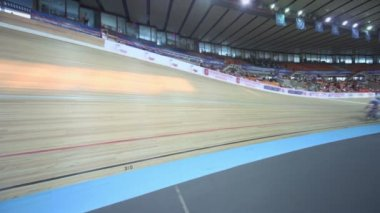 Several bicyclists ride track during race at stadium — Stock Video