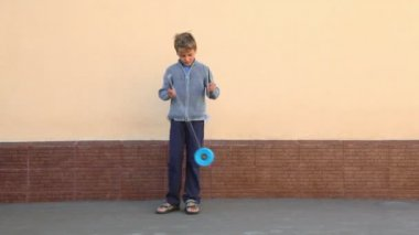 Little boy holds two sticks and plays toy near wall — Stock Video