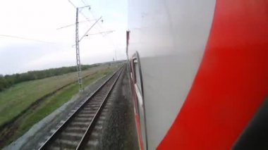 Red train goes along forest belt and rural areas, time lapse — Stock Video