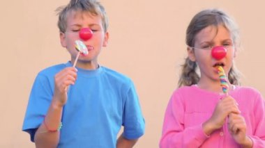 Two kids with clown noses eat colourful candies — Stock Video