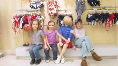 Two girls and boy sit near manikin in shopping center — Stock Video