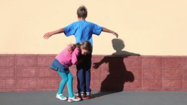 Girl rotates boy which spins with arms up sideward near wall — Stock Video