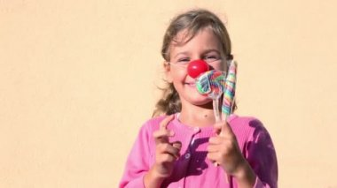 Girl with clown nose holds candies and choose which one to eat — Stock Video
