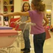 Stock Video: Two girls play with toy carriages for dolls in shop, time lapse