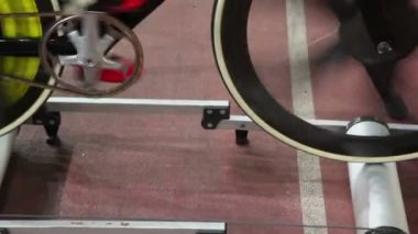 Cyclist spins pedals on bike at one place in rollers frame — Stock Video