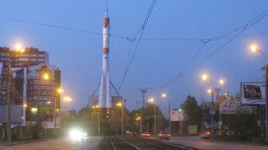 Monument rocket stands near passing cars in evening — Stock Video