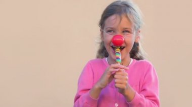 Little girl with clown nose sock colourful candy and smile — Stock Video