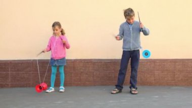 Two kids holds pairs of sticks and plays toy near wall — Stock Video