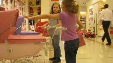 Zwei mädchen spielen mit spielzeug schlitten für puppen im zeitraffer-shop — Stockvideo