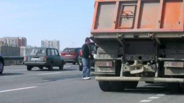 люди стоят после крушения на шоссе среди потока машин — Стоковое видео