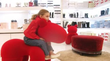 Zwei mädchen sitzen auf stuhl in form des pferdes von roten farbe, zeitraffer — Stockvideo