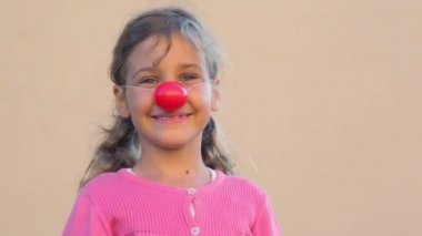Little girl with clown nose puts hands up and show tongue — Stock Video