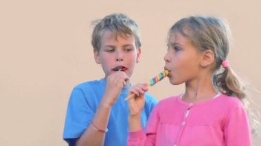 Two kids boy and little girl eat colourful candies and speak — Stock Video