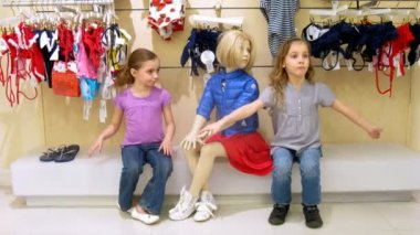 Dvě dívky a chlapce sedět vedle figuríny v nákupním centru, časová prodleva — Stock video