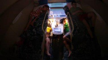 Familie van vier personen is in donkere compartiment in de trein — Stockvideo