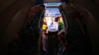 Family from four people is in dark compartment in train — Vidéo