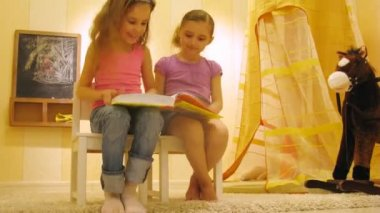 Two girls read book near toy horse in playroom — Stock Video