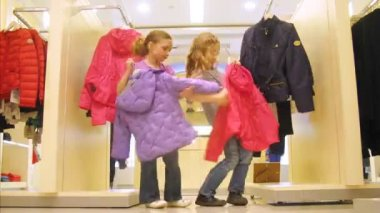 Two girls try on jackets in shopping center, time lapse — Stock Video