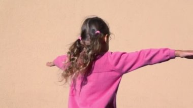 Little girls spins with arms up sideward near wall — Stock Video